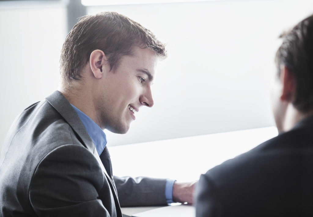Two business people smiling and looking down at a business meeting